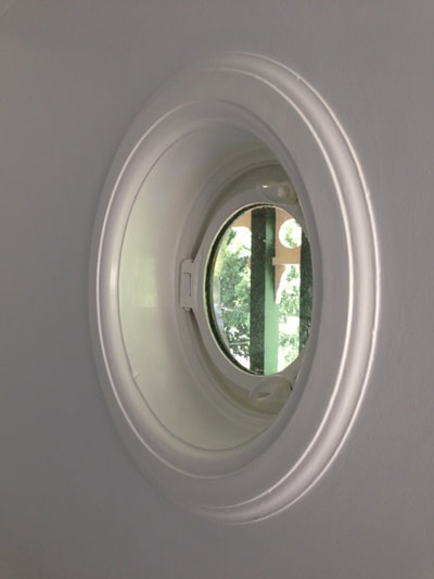 A beautiful painted window that is an actual ships porthole.