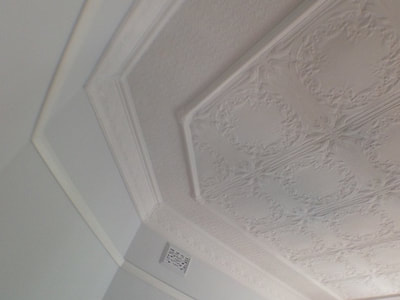 Painting historic moulded ceilings in flat white hides minor damage.